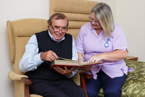 Resident and carer looking at photo album
